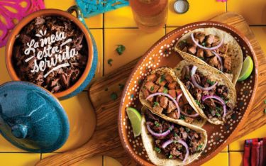 """La mesa esta servida"" in script written over the top of a crock of meat with a cutting board and four different tacos. – all on a colorful tile surface."