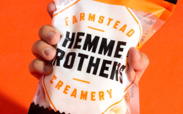 Hand holding Hemme Brothers Curds packaging