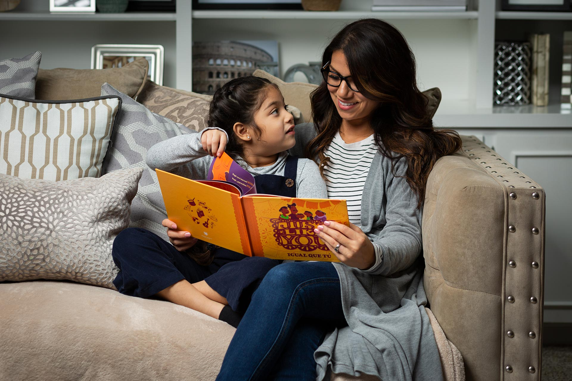Mother and daughter reading Just Like You book on a couch