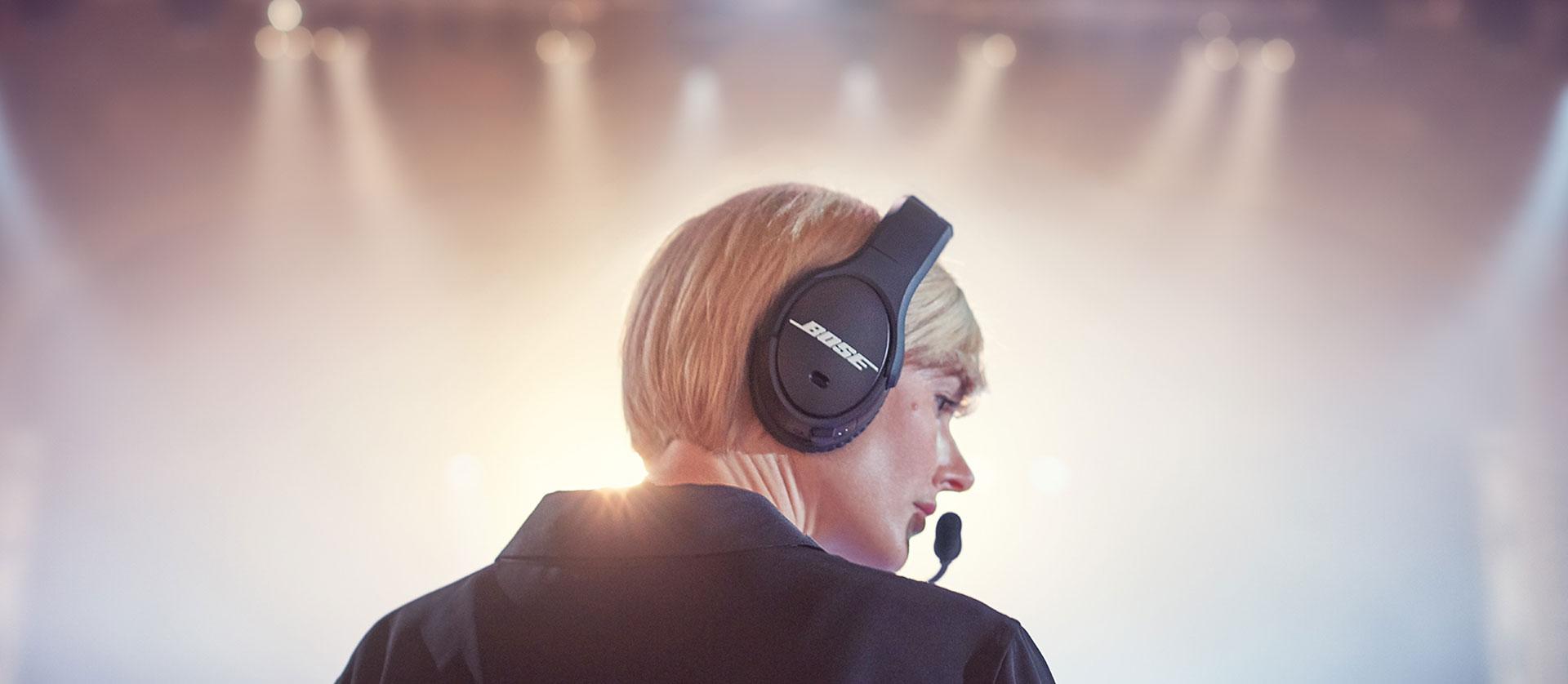 Female tech wearing Bose SoundComm B40 amid a backdrop of lights.