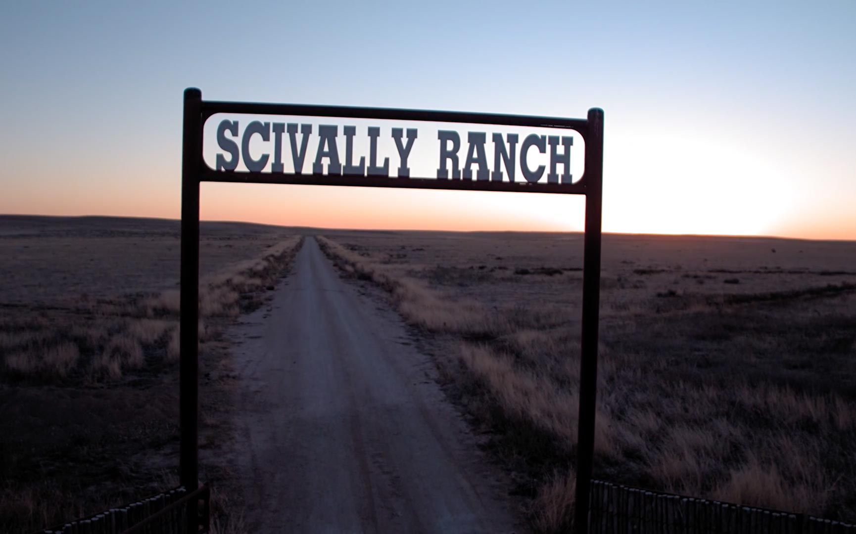 Straight road leading into the distance marked by Scivally Ranch sign over it.