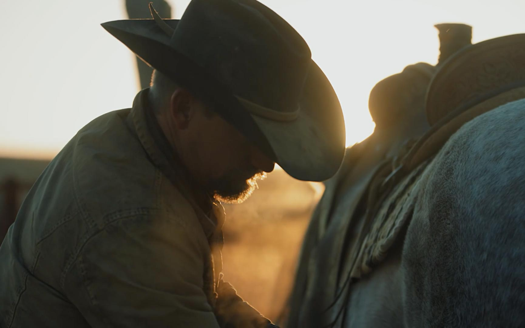 Close up of rancher adjust saddle on horse silhouetted against a sunset.