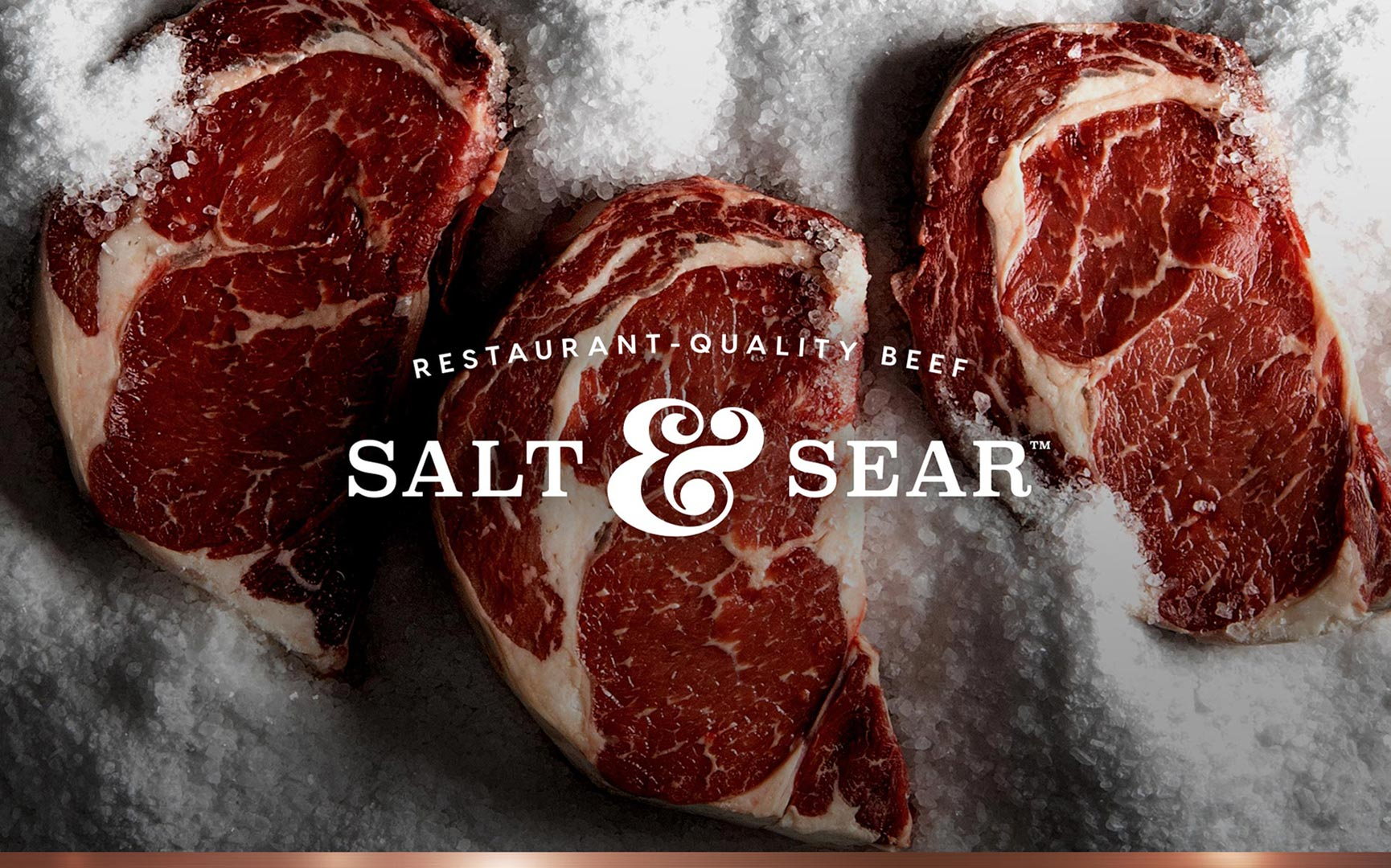 Salt & Sear Restaurant-Quality Beef branding. Logo emblazoned on ribeyes, embedded in salt.