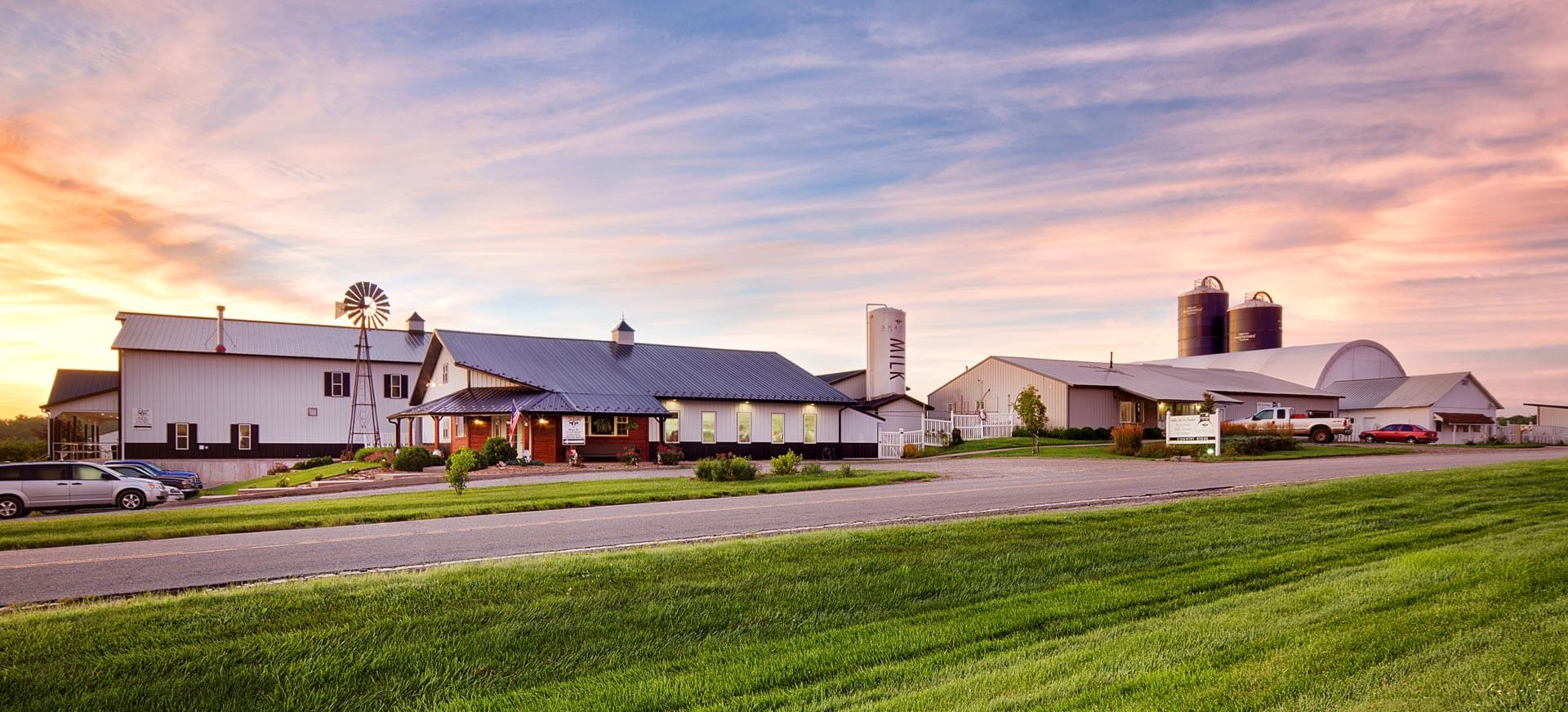 View of Shatto Milk Dairy buildings along a road with a golden sunset behind them.
