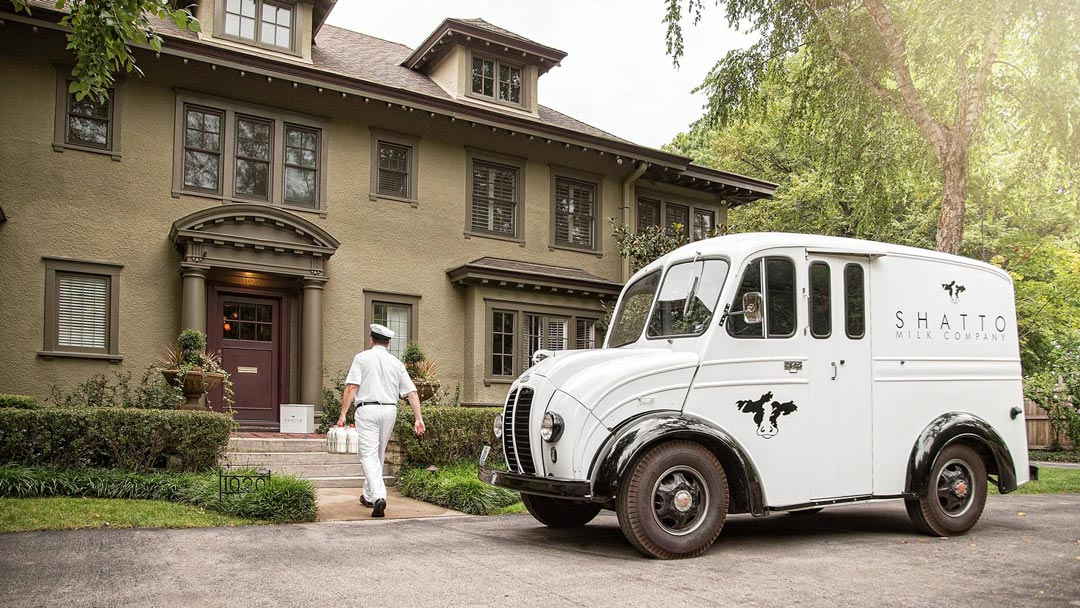 Vintage Shatto Milk Delivery Truck in front of home as milkman walks up to porch carrying fresh milk bottles.