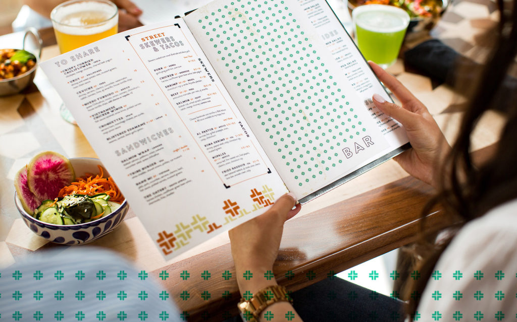 Over the shoulder view of hands holding open a Tribe Street Kitchen menu with beverages and bowls of food on the table behind it.