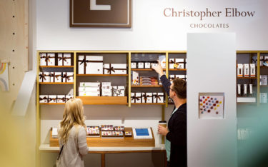 Christopher Elbow Chocolates store display with man and woman reaching for products off top shelf