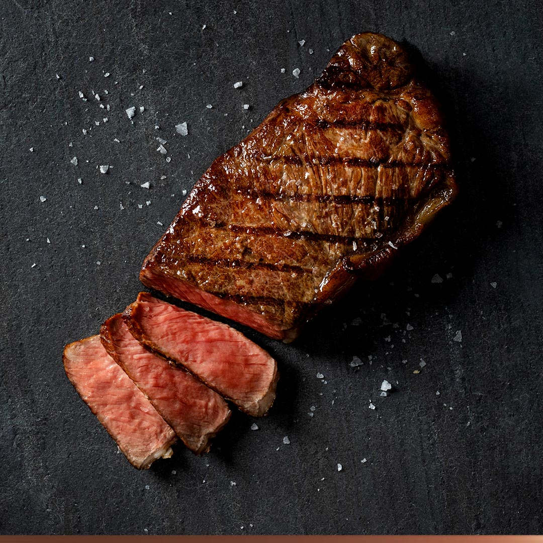 Grilled strip steak on a slate background surrounded by salt.