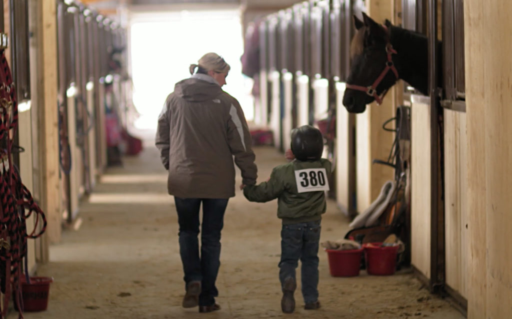 Mother holding hands with young daughter in riding gear as they walk away from us through a stable.