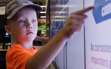Boy touching interactive Cargill wall