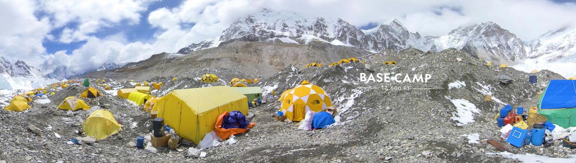 Panoramic view of Base Camp at Mount Everest with tents scattered about.